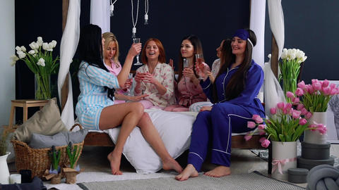 A group of young and beautiful girls in pajamas sitting on the bed with glasses Footage