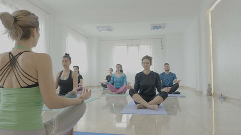 Yoga class made of middle aged women and man meditating in lotus position in a Footage