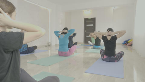 Middle aged women rotating heads sitting on a mat as a warm up exercises before Footage