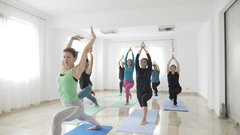 Women doing warrior yoga pose after work in a bright wellness studio in slow Footage