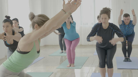 Strong attractive young female yoga instructor teaching middle aged women a new Footage