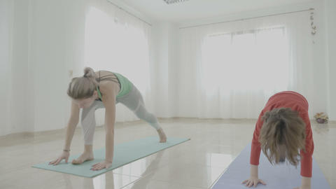 Young attractive mother female instructor teaching her daughter yoga poses in a Footage