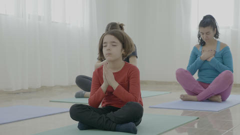 Little girl meditating among middle aged women during a yoga class in a fitness Footage