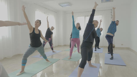 Yoga class made of middle aged women and a young man trying new poses and Footage