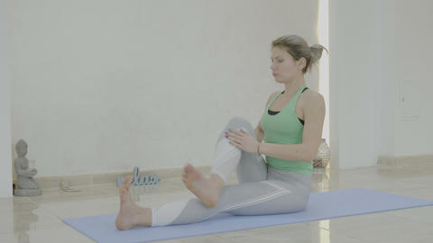 Beautiful attractive young woman staying fit and flexible by doing yoga poses on Footage