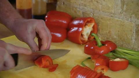 Cook cuts red sweet pepper on cutting board in slowmotion Live Action
