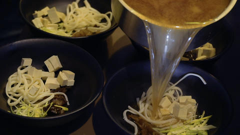 Chef pours meat bouillon and preparing miso soup in korean restaurant Footage