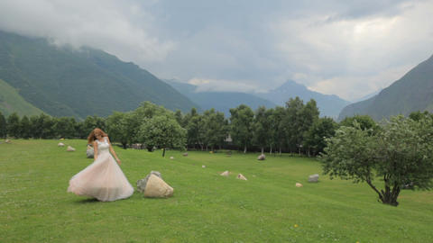 red-haired bride in a lavish dress walks along the green grass against the Footage