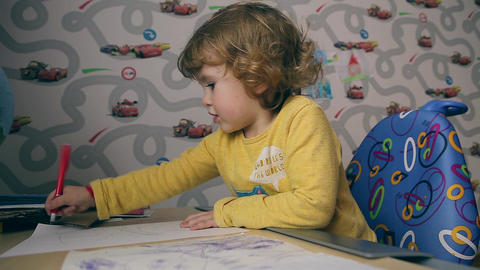 Little beautiful girl draws at the desk Footage