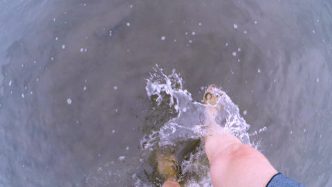 POV of a woman with painted toe nails walking through shallow ankle deep water Footage