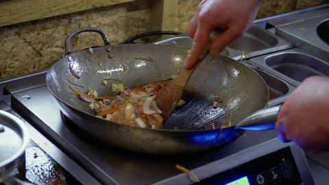 Chef mixes rice noodles and fried vegetables with spatula in a hot pan Footage