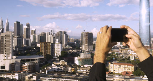 Push out of a male tourist taking photos of a modern city outside with his smart Footage