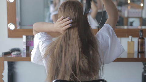Woman drying hair in front of a mirror Live Action