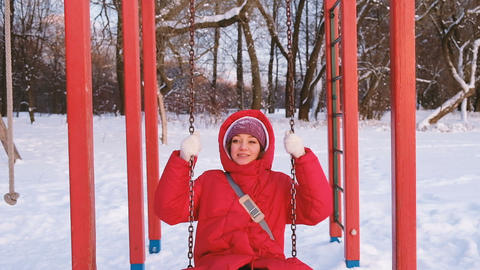 An adult girl in a red down jacket swinging on a red swing in the playground at Footage