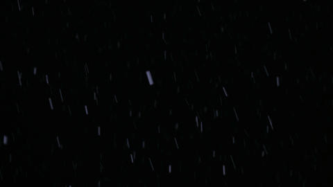 Long snow flakes fall against the background of the night sky under the light of Footage