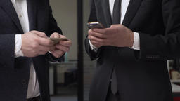 Two businessmen in suits stand in the office and using smartphones. 60 fps Footage