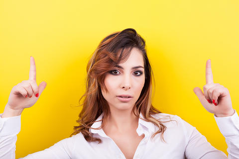 Brunette woman pointing up with both hands Photo