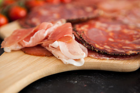 Meat antipasto appetizers lying on wooden table Photo