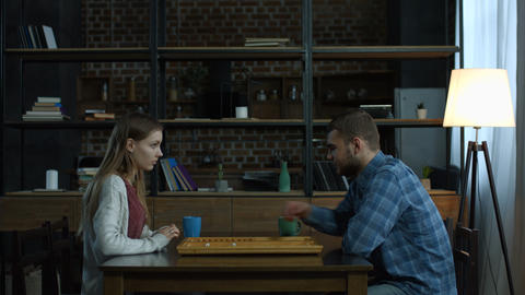 Young positive couple playing backgammon at home Footage