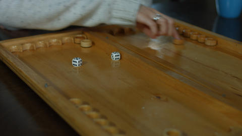 Playing backgammon on a wooden table with dice Footage
