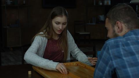 Joyful charming girl playing backgammon at home Footage