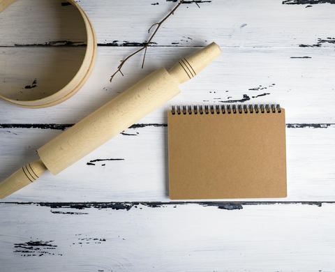 notebook and a wooden rolling-pin with a round wooden sieve Photo