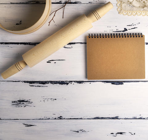 open blank notebook with brown pages and a wooden rolling-pin wi Photo