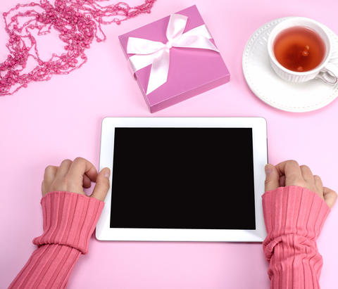 female hands holding an electronic tablet with an empty black sc Photo