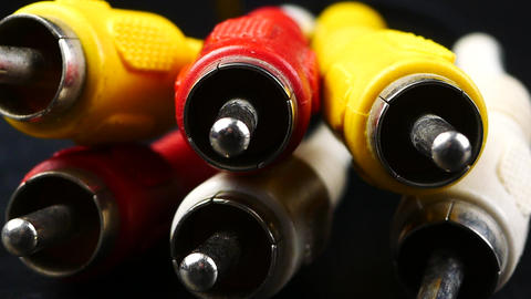 red, white and yellow male cinch plugs, on black background Live Action