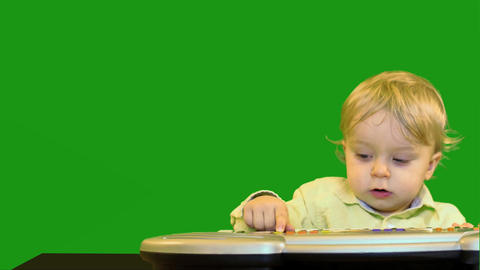 cute 1 year old baby near electronic synthesizer green screen dolly shot Footage