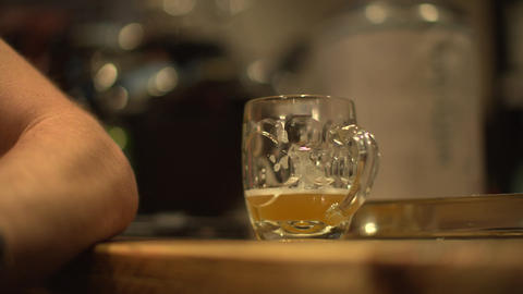 A shot of a glass of beer next to a mans arm on a bar in pub Live Action