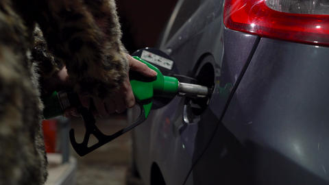 Woman fills petrol into her car at a gas station in winter Footage