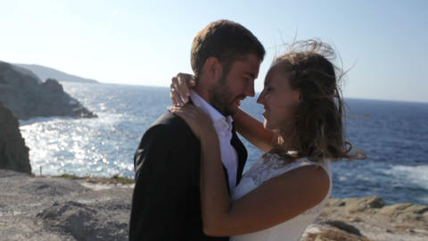 Bride and groom kissing by the sea on their wedding day Footage