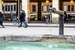 Munich / Germany - February 15 2018 : Water flowing from well while People Photo