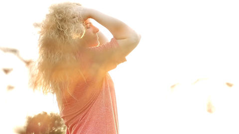 Beautiful girl with curly hair posing on the camera. Slow-motion filming. Sunset Footage