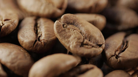 Close up of coffee beans. In front of the camera rotates plate with coffee beans Footage