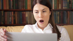 Businesswoman using laptop at home, professional female receiving good news Footage