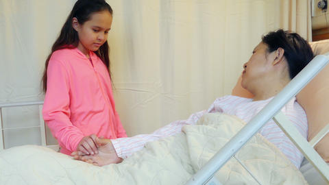 Daughter holds sick mother's hand in hospital bed pull in Live影片