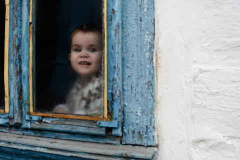 A little girl sits in an old hut on a window on which the paint faded Fotografía