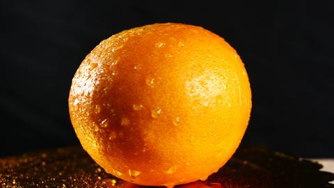 Orange rotate on black background Footage