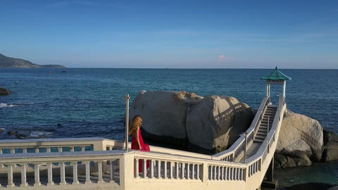 Girl Goes down on Bridge against Stunning Seascape Live Action