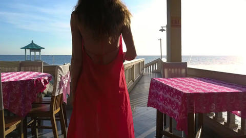 Girl in Red with Selfie Stick Walks along Tables Footage