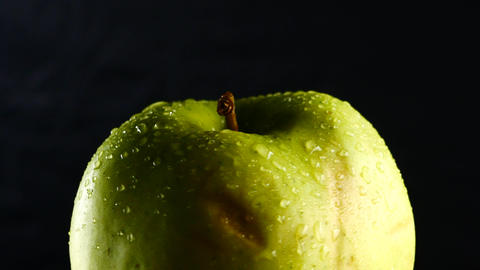 green apple with water drops rotates on black background Footage