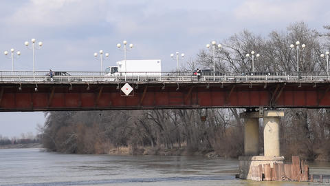 Automobile bridge over the river. On the bridge cars go and people go Footage