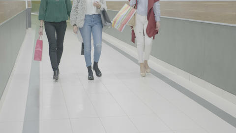 Fashion styled girl friends marching at the mall with shopping bags in their Footage