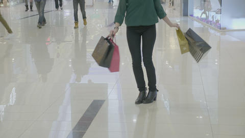 Close up of funny happy woman in heels carrying shopping bags walking in a Footage