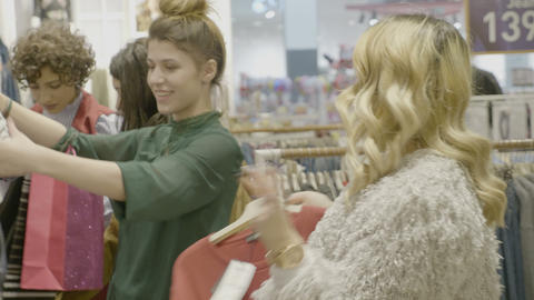 Happy styled female friends checking a designer bag an looking at clothing items Footage