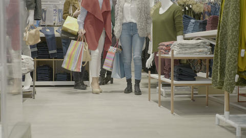 Young attractive female shoppers looking at clothes in a mall store and walking Footage