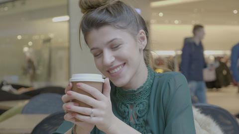 Female sales manager resting after work drinking cappuccino in a shopping center Footage