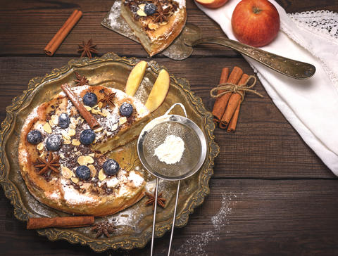 baked round apple pie and iron sieve with powdered sugar Photo